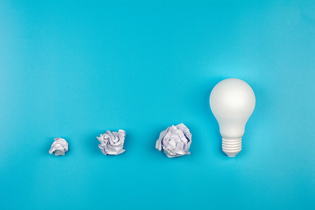 Brainstorming image of crumbled paper and a light bulb